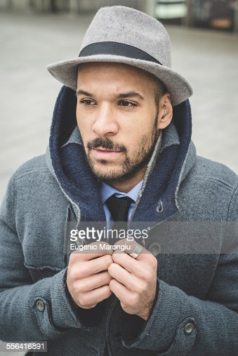Businessman fastening his coat