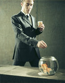 Businessman feeding goldfish