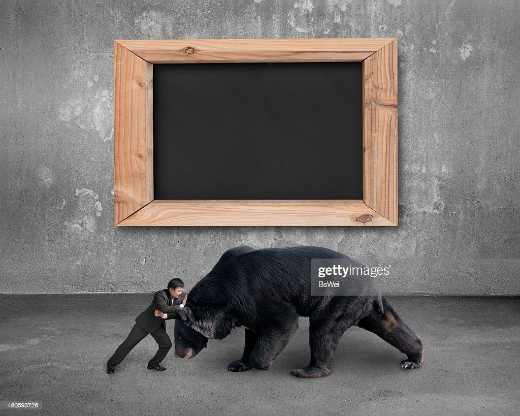 Businessman fighting against black bear with blank blackboard : Stock Photo