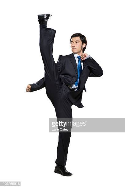 Businessman fighting stance with leg in the air