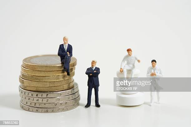 Businessman figurine with coins and figurines of doctors with pills