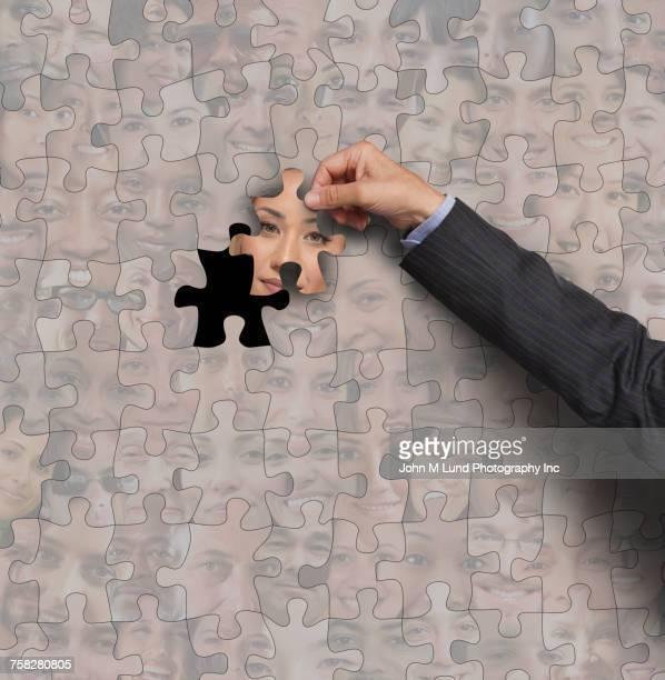 Businessman finishing jigsaw puzzle of human faces