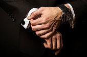 Businessman Fixing Cuff links ,studio shoot