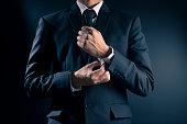Businessman Fixing Cufflinks his Suit