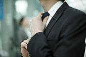 businessman fixing tie