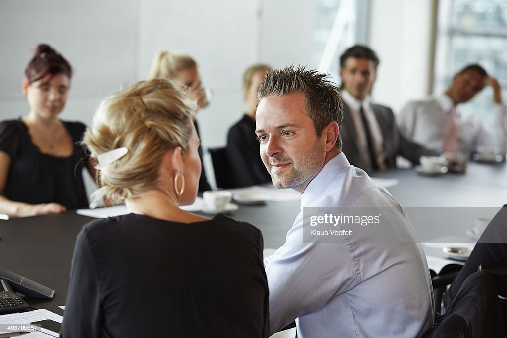 Businessman flirting with coworker at meeting : Stock Photo