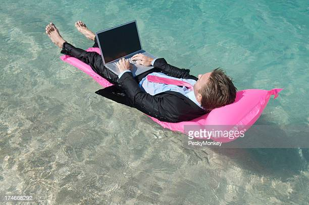 Businessman Floats on Pink Air Mattress Tropical Sea with Laptop