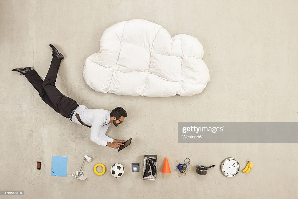 Businessman flying between cloud shape pillow and variety of items : Stock Photo