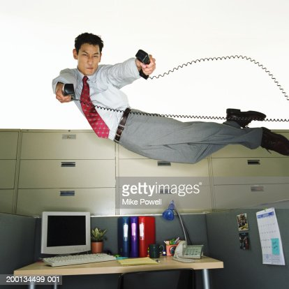 Businessman flying over desk, holding telephone receivers : Stock Photo