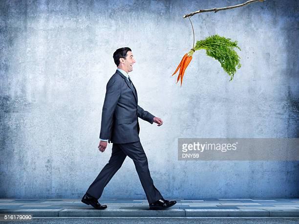 Homme d'affaires suit les carottes pendre un bâton