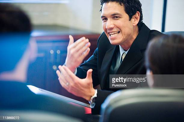 Businessman forcefully gesturing towards his colleagues
