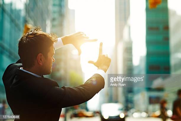 Businessman framing sun on city street.