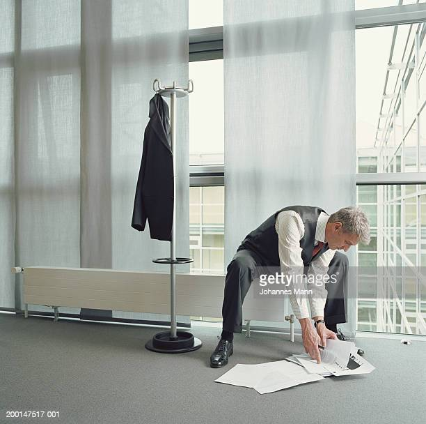 Businessman gathering papers from office floor