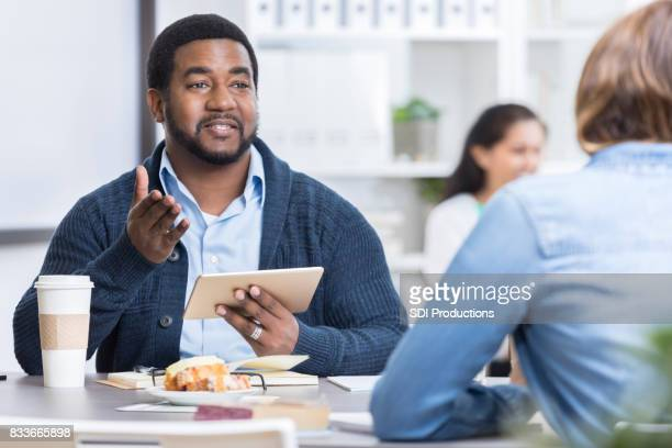 Businessman gestures while using digital tablet during business meeting