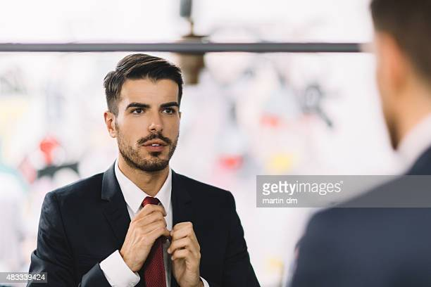 Businessman getting dressed in front of the mirror