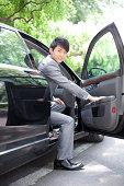 Businessman getting off car