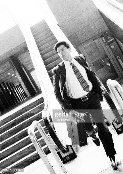 Businessman getting off escalator, holding briefcase, blurred, b&w.