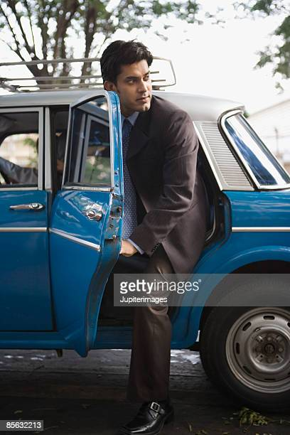 Businessman getting out of or into taxi cab
