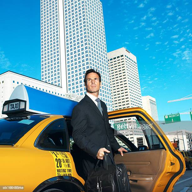 businessman getting out of taxi near office buildings