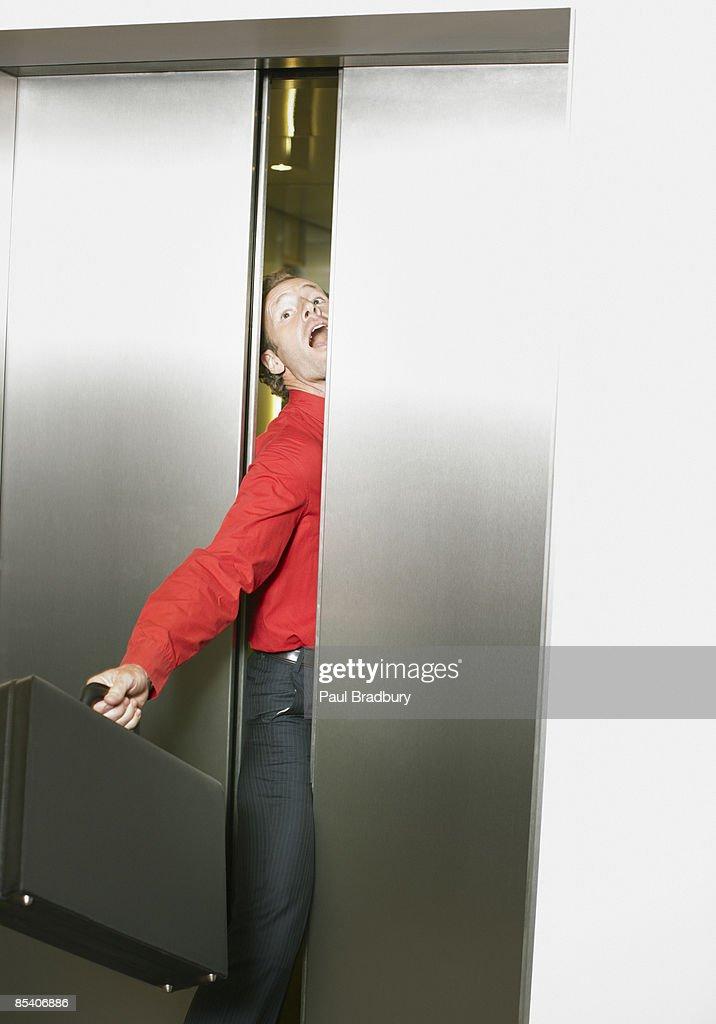 Businessman getting stuck in elevators doors