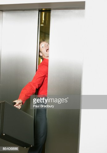 Businessman getting stuck in elevators doors : Stockfoto