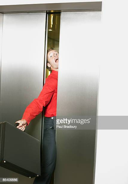 Businessman getting stuck in elevators doors