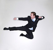 Businessman gives a karate kick in the air inside the office