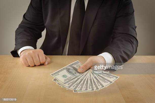 Businessman giving a stuck of money