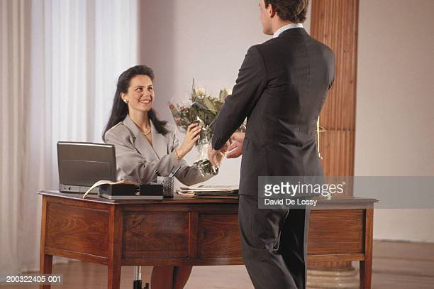 Businessman giving bouquet to mid adult woman