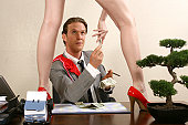 Businessman giving dollar bills to a woman standing on a desk