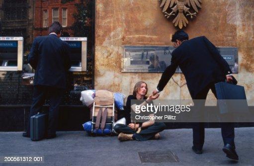 Businessman giving money to beggar sitting beside ATM