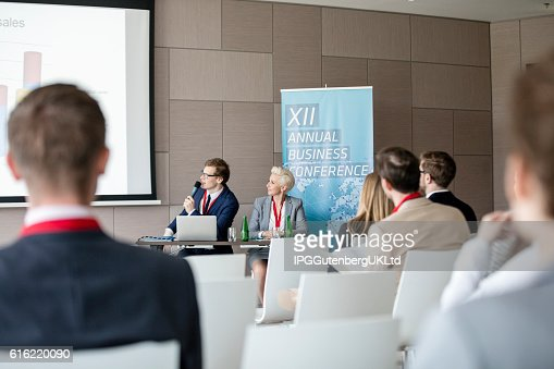 Businessman giving presentation in seminar hall : Stock Photo