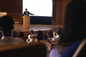 Front view of mixed race businessman giving presentation on white projector in front of the audience
