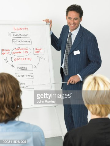 Businessman giving presentation, smiling, colleagues in foreground : Foto de stock
