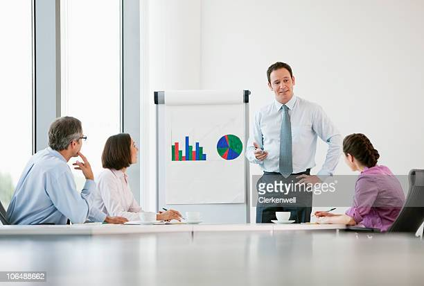 Businessman giving presentation through graph to colleagues in conference room