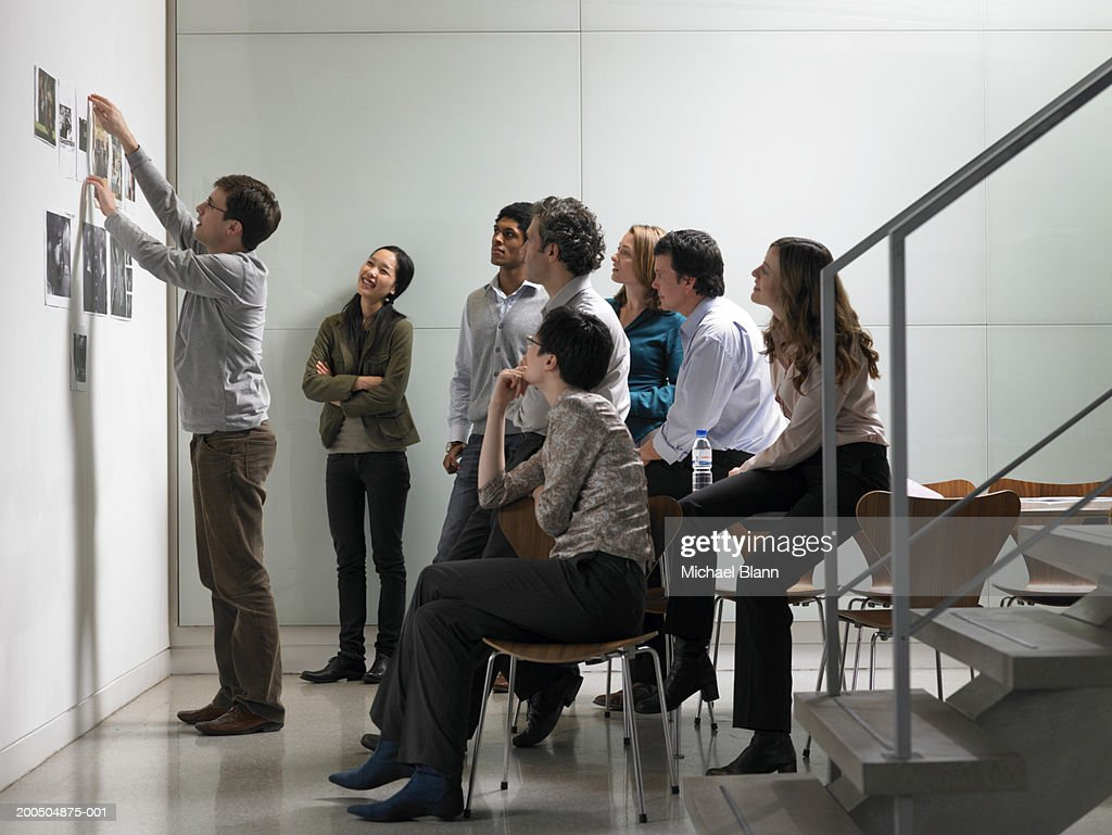 Businessman giving presentation to colleagues in board room : Stock Photo