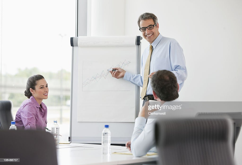 Businessman giving presentation to his colleagues at office : Stock Photo