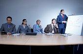 Businessman giving presentiation in boardroom, colleagues looking away