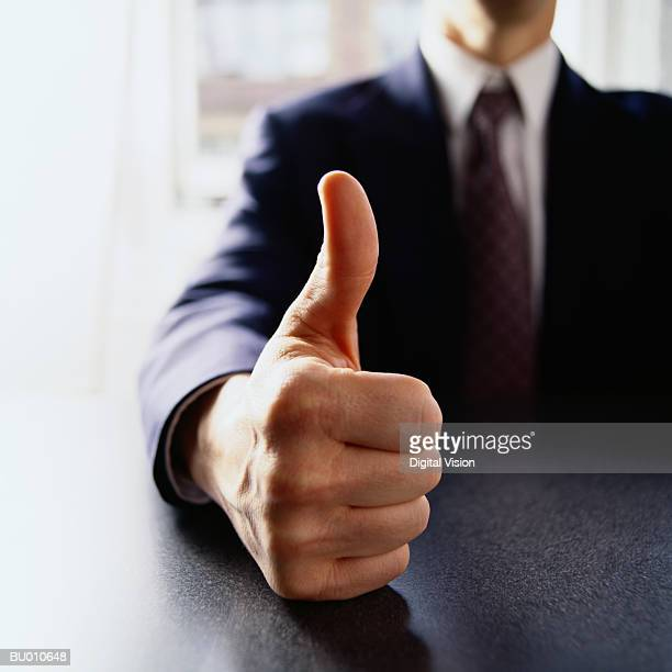 Businessman giving thumbs up sign, close-up
