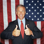 Businessman giving thumbs-up sign in front of American flag, smiling