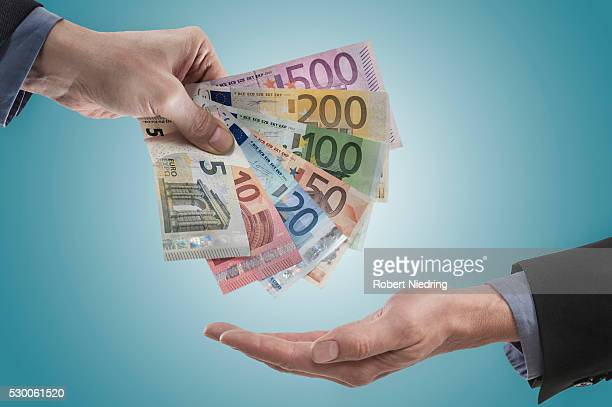 Businessman giving wages his employee, Bavaria, Germany