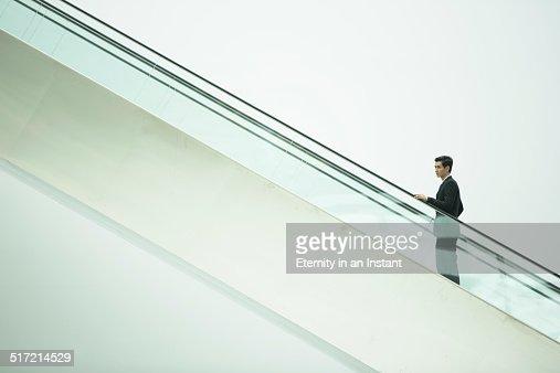 Businessman going up an escalator.