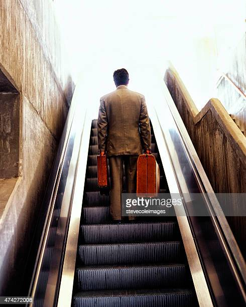 Businessman going up escalator with luggage.
