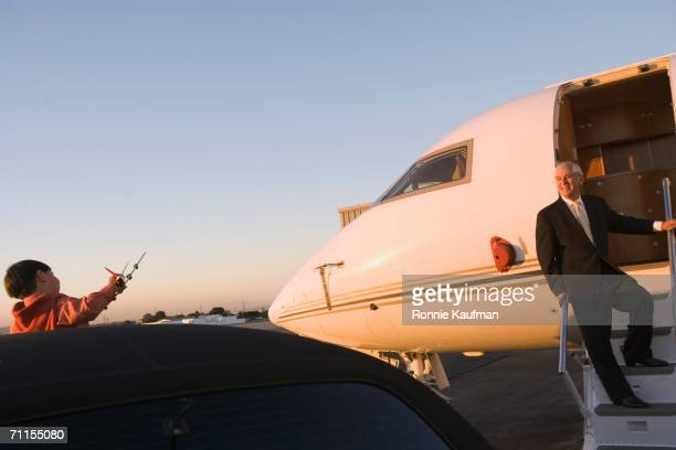 Businessman greeting son from plane