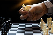 Businessman grip many Chess Piece in the hand  to play chess concept business strategy for win