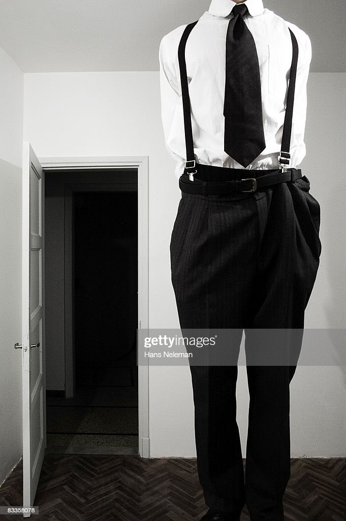 Businessman growing out of a room : Stock Photo