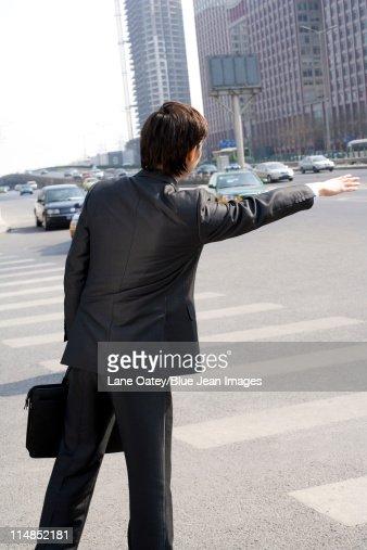 Businessman hailing a taxi : Stock Photo