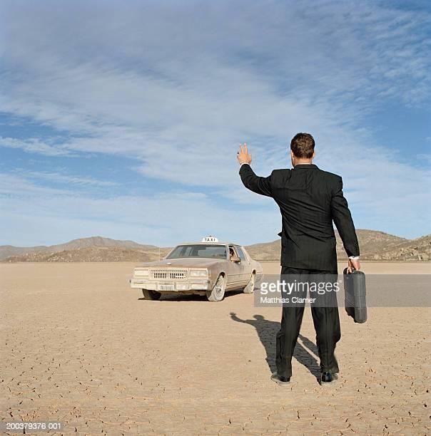 Businessman hailing taxi in desert, rear view