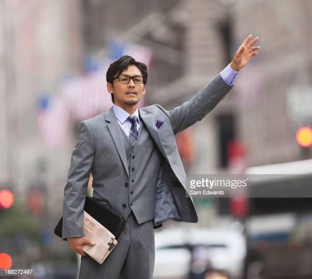 Businessman hailing taxi on city street