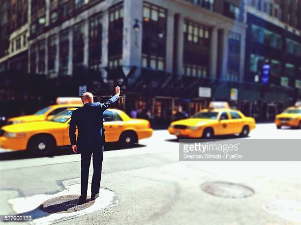 Businessman Hailing Taxi On City Street